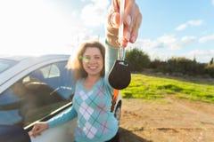 Счастливый водитель женщины показывая ключи автомобиля на предпосылке ее автомобиля Стоковое Фото