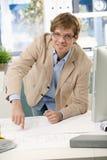 Счастливый вскользь инженер указывая на план на таблице Стоковая Фотография