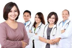 Счастливый гордый пациент стоя в фронте группа в составе доктор стоковые фото