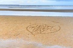 Счастливый День матери написанный в песке Стоковые Изображения