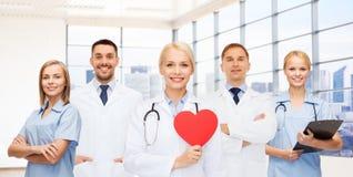Счастливый детеныш врачует кардиологов с красным сердцем Стоковая Фотография RF