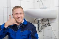 Счастливый делать водопроводчика вызывает меня жестом Стоковые Фото