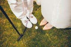 Счастливый жених и невеста играя гольф - близкую поднимающую вверх свадьбу стоковые изображения