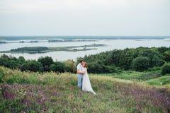 Счастливый жених и невеста идя на зеленую траву Стоковое фото RF