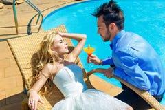 Счастливый жених и невеста наслаждается безграничностью poolside коктеиля тропик Стоковое Изображение RF