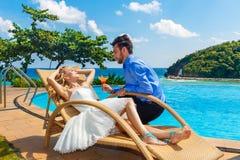 Счастливый жених и невеста наслаждается безграничностью poolside коктеиля тропик Стоковая Фотография RF