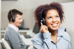 Счастливый женский агент центра телефонного обслуживания используя шлемофон внутри стоковые фотографии rf