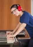 Счастливый женский плотник используя Tablesaw стоковая фотография
