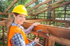 Счастливый женский работник бить молотком ноготь молотком на рамке тимберса стоковое изображение