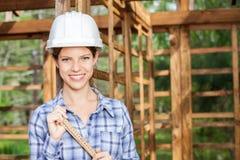 Счастливый женский работник держа измеряя ленту на месте Стоковые Фото