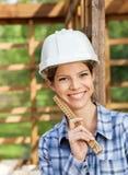 Счастливый женский работник держа измеряя ленту на месте Стоковые Изображения RF