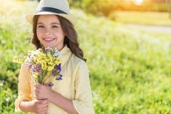 Счастливый женский ребенк с букетом на луге Стоковое Изображение