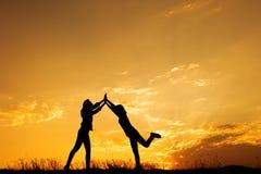 Счастливый 2 женщин хлопая и силуэта захода солнца стоковые изображения