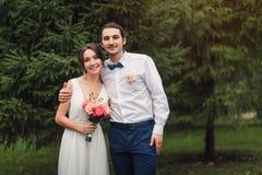 Счастливый жизнерадостный усмехаться как раз пожененные пары стоя в парке Стоковое фото RF