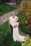 Счастливый жизнерадостный усмехаться как раз пожененные пары стоя в парке Стоковое Изображение RF