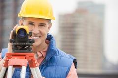 Счастливый зрелый рабочий-строитель с теодолитом