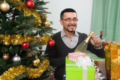 Счастливый зрелый человек около рождества в живущей комнате Стоковая Фотография