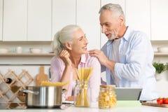 Счастливый зрелый человек стоя около зрелой жизнерадостной женщины используя таблетку Стоковая Фотография