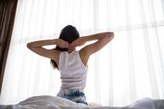 Счастливый здоровый взгляд задней части ` s женщины просыпая вверх протягивать в интерьере гостиницы или дома комнаты кровати на  Стоковая Фотография
