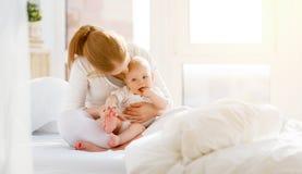 Счастливый играть матери и младенца семьи, обнимая в кровати стоковая фотография rf
