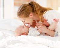 Счастливый играть матери и младенца семьи, обнимая в кровати стоковая фотография