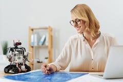 Счастливый изобретатель работая в студии стоковые изображения