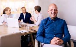 Счастливый и гордый бизнесмен представляя его команду сидя за им стоковое изображение