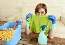 Счастливый и жизнерадостный представлять живущей комнаты женщины или домохозяйки очищая шаловливый с тканью Стоковое Изображение
