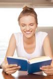 Счастливый и усмехаясь девочка-подросток с книгой Стоковые Фото