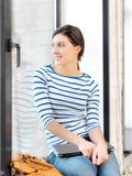 Счастливый и усмехаясь девочка-подросток с компьтер-книжкой Стоковые Фото