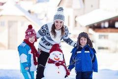 Счастливый красивый снеговик здания семьи в саде, зимнее время, Стоковое Изображение RF