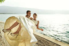 Счастливый красивый groom держа невесту в его оружиях на пляже на sunse Стоковое фото RF