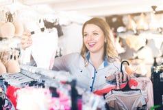 Счастливый клиент женщины выбирая бюстгальтер Стоковые Изображения RF