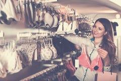 Счастливый клиент женщины выбирая милое женское бельё Стоковая Фотография RF