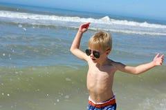 Счастливый маленький ребенок играя в океане стоковое изображение