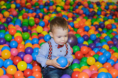 Счастливый маленький ребенок играя на красочной пластичной спортивной площадке шариков Стоковые Фотографии RF