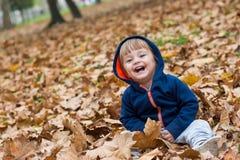 Счастливый маленький ребенок, ребёнок смеясь над и играя в осени Стоковые Изображения RF