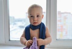 Счастливый маленький ребёнок стоя около окна weared в шляпе зимы и шарфе, городе на предпосылке стоковое фото rf