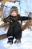 Счастливый малыш 2 год сидя на дереве в зиме стоковое изображение
