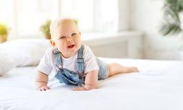 Счастливый малыш младенца в кровати Стоковое Фото
