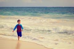 Счастливый мальчик бежать на пляже песка Стоковое фото RF