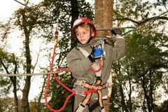 Счастливый мальчик взбираясь в парке приключения Стоковые Изображения
