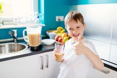 Счастливый мальчик выпивает selfmade коктеиль плодоовощ Стоковая Фотография RF