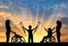 Счастливый мальчик в кресло-коляске и мальчик стоя с костылями инвалидом и заходом солнца медсестер Стоковое Изображение RF