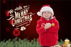 Счастливый мальчик в шляпе santa держа безделушки рождества Стоковая Фотография RF