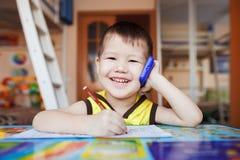 Счастливый мальчик говоря на smartphone дома стоковое изображение