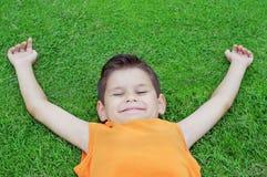 Счастливый мальчик лежа на зеленой траве стоковые фотографии rf