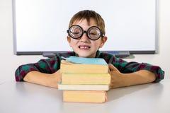 Счастливый мальчик держа книги на таблице в классе Стоковая Фотография