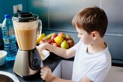 Счастливый мальчик делает здоровый фруктовый сок дома Стоковые Изображения