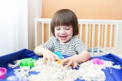 Счастливый мальчик играет кинетический песок дома стоковое изображение